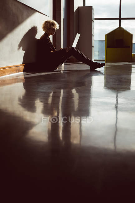 Young woman using laptop in library sitting on the floor — Stock Photo