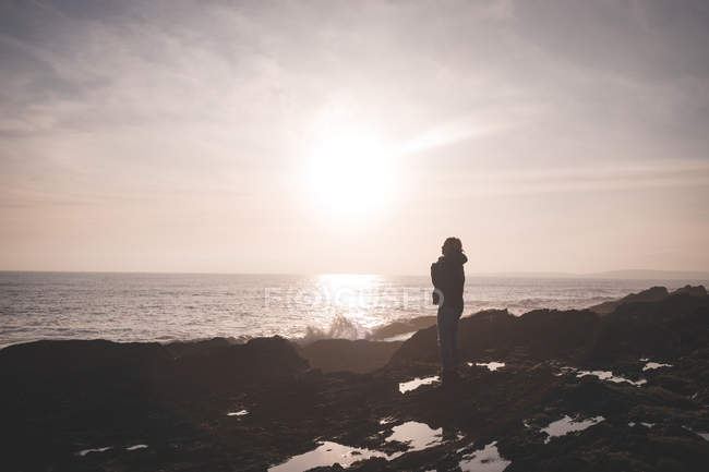 Silhouette of woman standing on a beach at dusk — Stock Photo