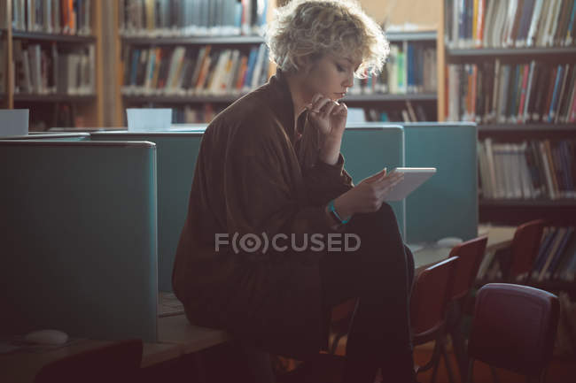 Young Woman Using Digital Tablet In biblioteca — Foto stock