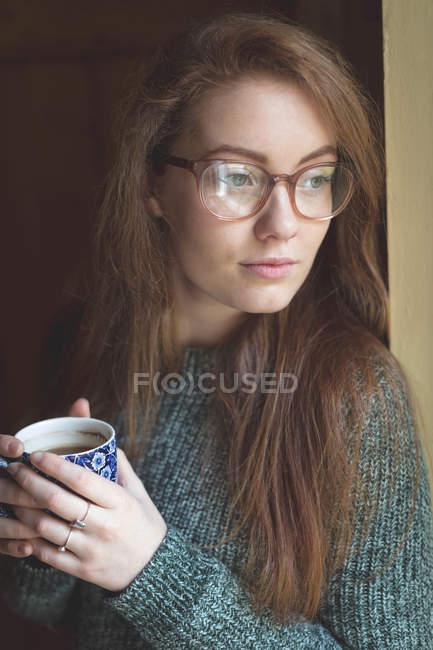 Donna premurosa che beve caffè nero a casa — Foto stock