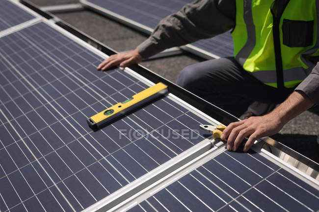 Mid section of male worker working on solar panels at solar station — Stock Photo