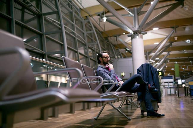 Задумчивый бизнесмен ждет в зале ожидания аэропорта — стоковое фото