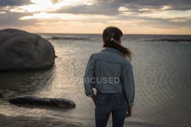 Задня погляд жінки, дивлячись на вид на пляжі в сутінках — стокове фото