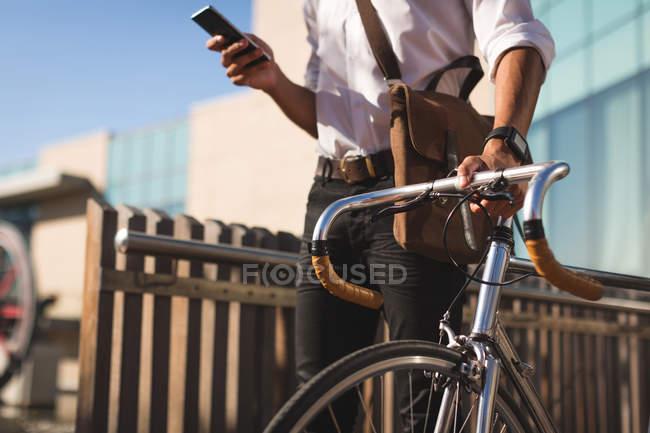 Homme d'affaires utilisant un téléphone portable tout en marchant avec son vélo dans les locaux du bureau — Photo de stock