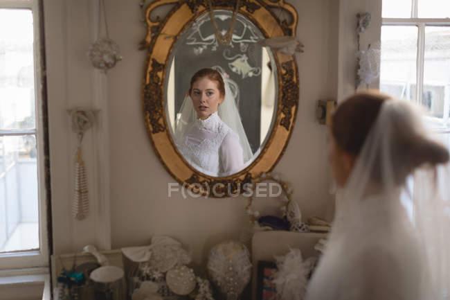 Noiva branca no vestido de noiva e véu olhando no espelho vintage boutique — Fotografia de Stock