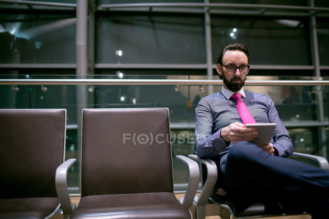 Businessman using digital tablet in waiting area at airport — Stock Photo