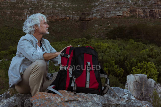 Senior hiker sitting on a rock in countryside — Stock Photo