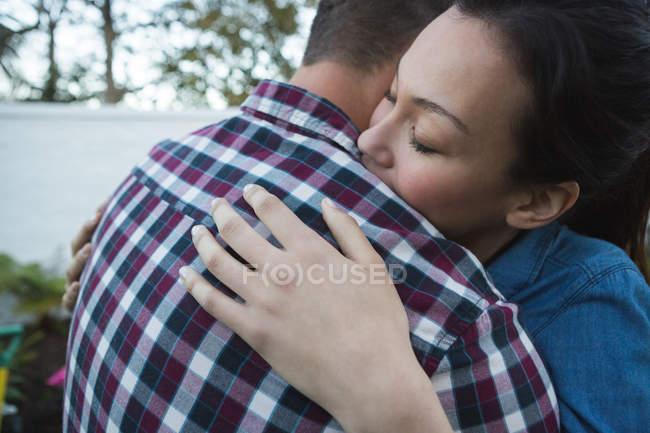Romántica pareja abrazándose unos a otros en el jardín - foto de stock