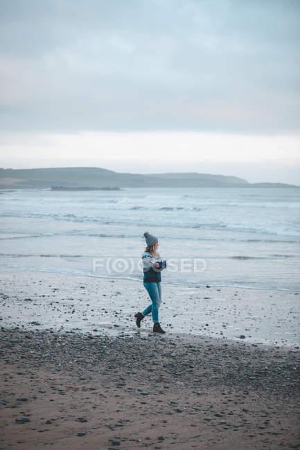 Mulher andando em uma praia ao entardecer — Fotografia de Stock