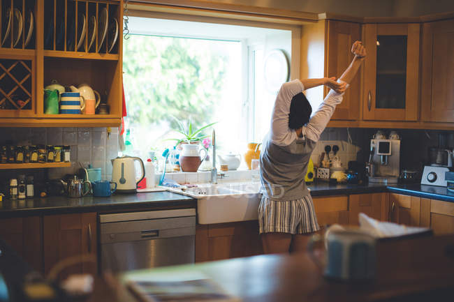 Rear view of woman standing with arms up in kitchen at home — Stock Photo