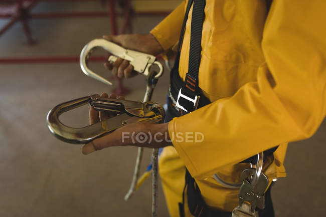 Midsection of male worker holding carabiner at solar station — Stock Photo