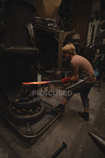 Blacksmith shaping hot metal rod in machine at workshop — Stock Photo