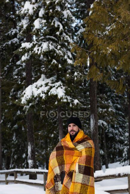 Молодой человек, завернутый в одеяло зимой — стоковое фото