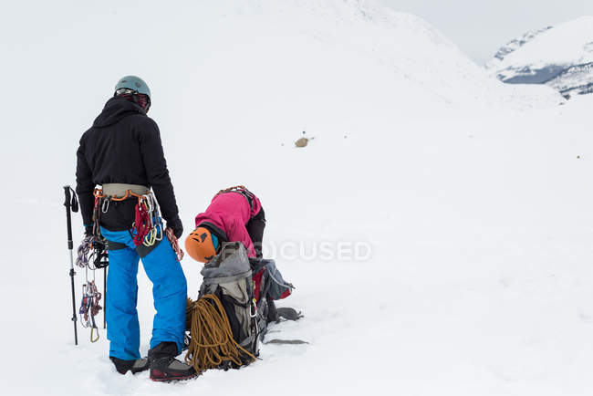 Couple standing with backpack and harness on a snow covered mountain during winter — Stock Photo