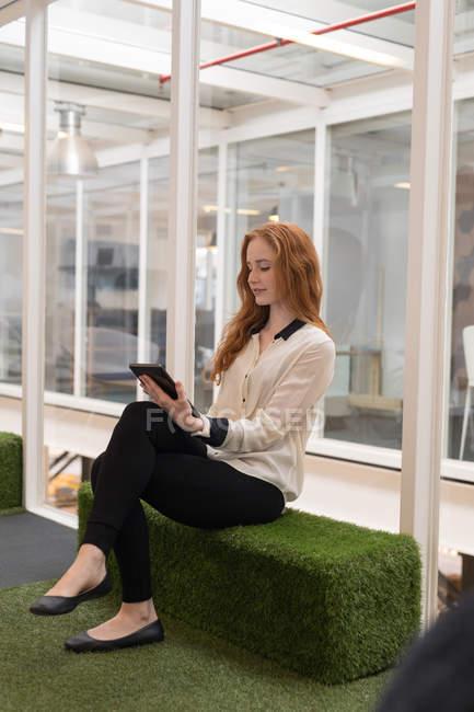 Молодая женщина-руководитель с помощью цифрового планшета в офисе — стоковое фото
