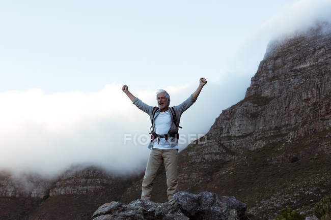 Senior hiker standing with arms up in forest at countryside — Stock Photo