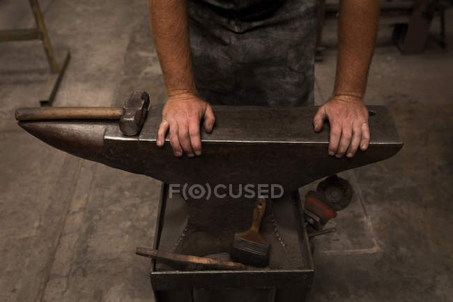 Blacksmith standing with hands on anvil in workshop — Stock Photo