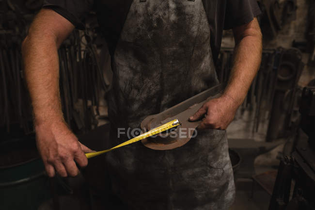 Blacksmith measuring a metal with measuring tape in workshop — Stock Photo