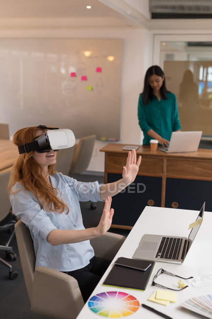 Female graphic designer using virtual reality headset in office — Stock Photo