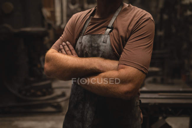 Mid section of blacksmith standing with arms crossed in workshop — Stock Photo