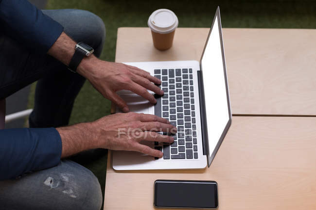 Cropped image of businessman using laptop in office — Stock Photo