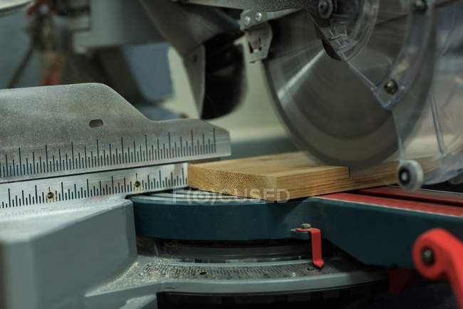 Grinder cutting machine cutting a piece of wood at workshop — Stock Photo