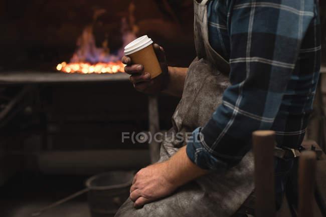 Средняя секция кузнеца пьет кофе в мастерской — стоковое фото