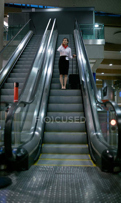 Woman standing on escalator with luggage at airport — Stock Photo