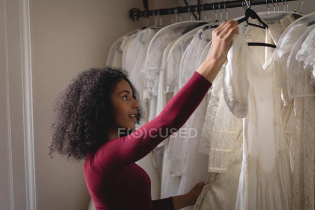 Mulher selecionando vestido de noiva de cabides de roupas na boutique — Fotografia de Stock
