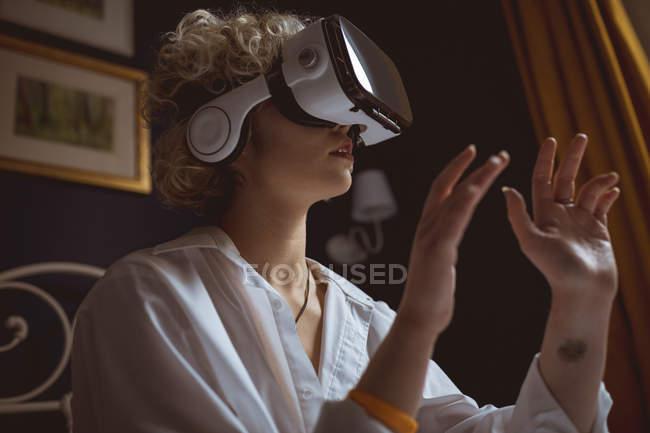 Frau benutzt Virtual-Reality-Headset im Schlafzimmer zu Hause — Stockfoto