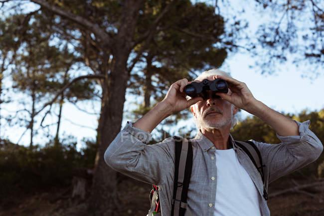 Escursionista anziano guardando attraverso binocoli nella foresta in campagna — Foto stock