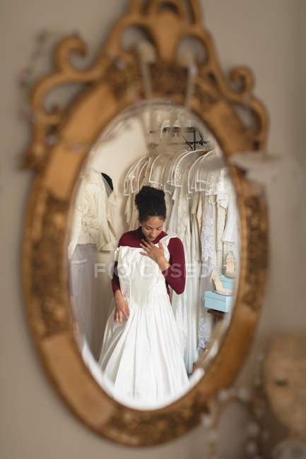 Reflexo da noiva casamento tentando vestir de cabide no espelho na boutique — Fotografia de Stock