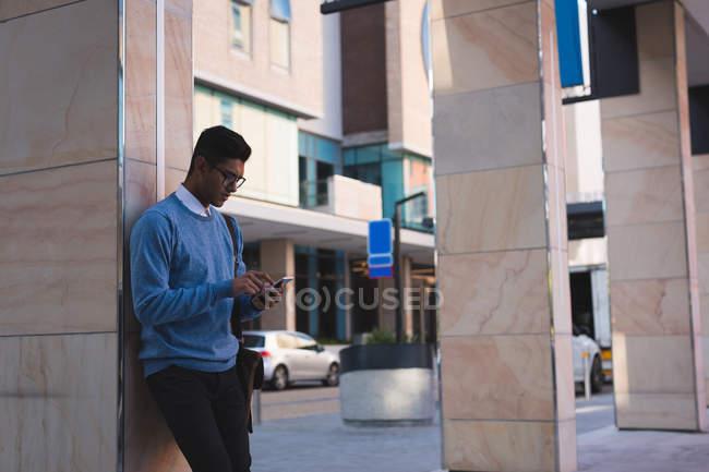 Homme d'affaires utilisant un téléphone portable à l'extérieur des locaux du bureau par une journée ensoleillée — Photo de stock