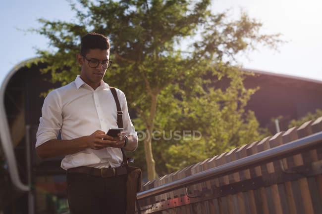 Homme d'affaires utilisant un téléphone portable à l'extérieur par une journée ensoleillée — Photo de stock