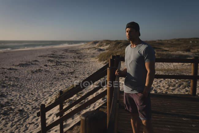 Surfista maschio in piedi con il surf vicino alla spiaggia in una giornata di sole — Foto stock