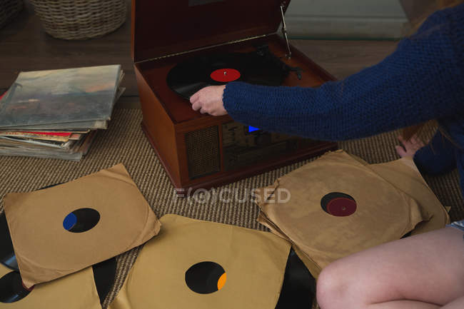 Mid section of woman playing a gramophone at home — Stock Photo