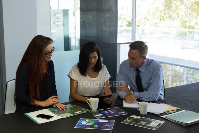 Business colleagues working on digital tablet in office — Stock Photo