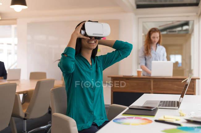 Diseñadora gráfica femenina usando auriculares de realidad virtual en la oficina - foto de stock
