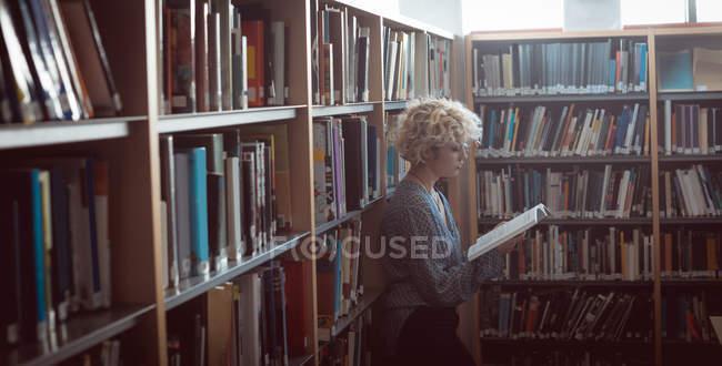 Jeune femme lisant un livre à la bibliothèque — Photo de stock