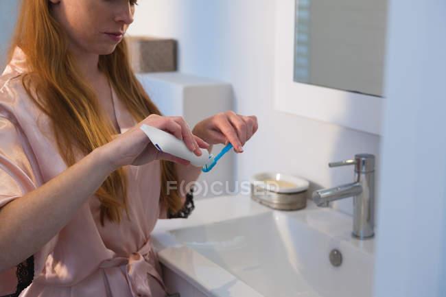 Mulher aplicando pasta de dentes na escova de dentes no banheiro em casa — Fotografia de Stock