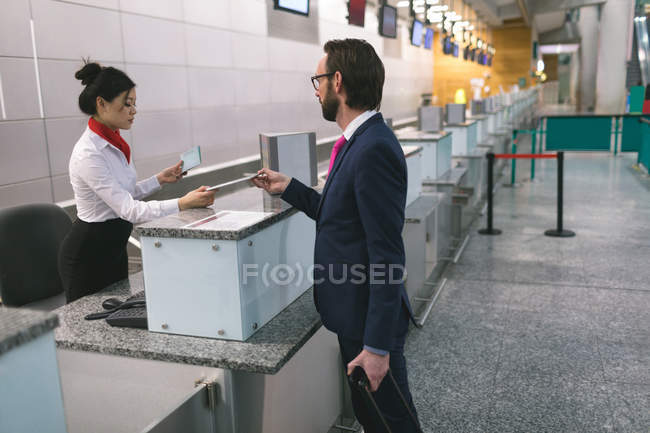 Airline check-in attendant handing digital tablet to commuter at counter in airport terminal - foto de stock