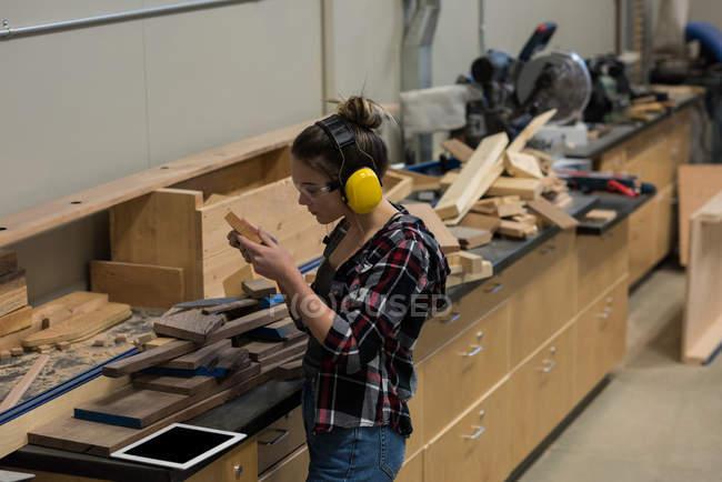 Menuisière examinant un morceau de bois à l'atelier — Photo de stock