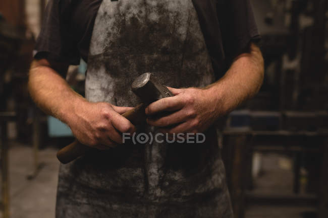 Mid section of blacksmith holding a hammer in workshop — Stock Photo
