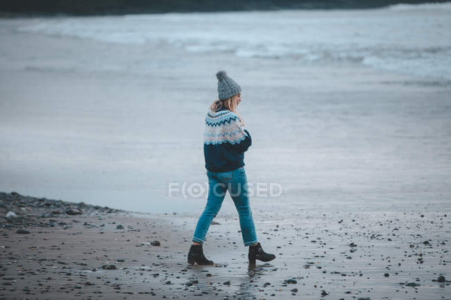 Woman walking on a beach at dusk — Stock Photo