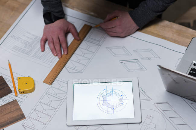 Male carpenter drawing a chart on chart paper at workshop — Stock Photo