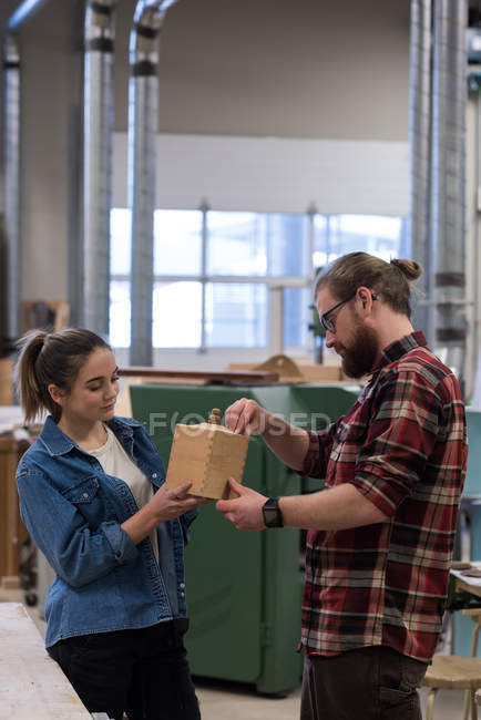 Male and female carpenters examining a piece of wooden furniture at workshop — Stock Photo