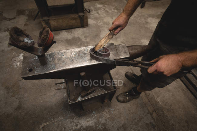 Blacksmith using hand wire brush on metal rod in workshop — Stock Photo