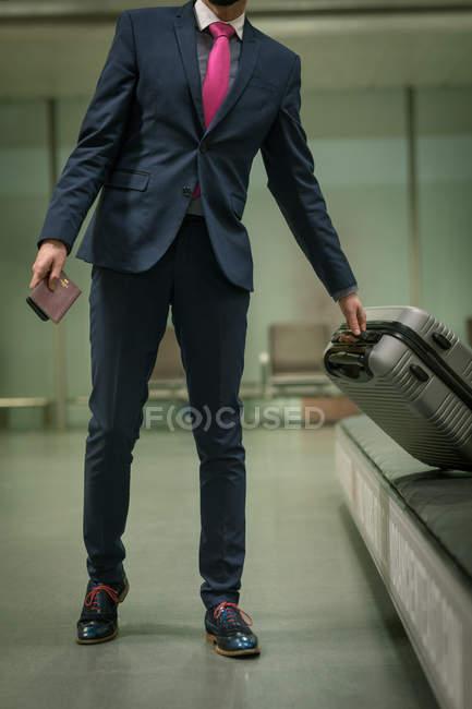 Homme d'affaires prenant leurs bagages du carrousel à bagages à l'aéroport — Photo de stock