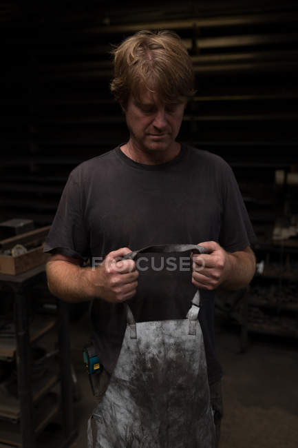 Thoughtful blacksmith wearing apron in workshop — Stock Photo