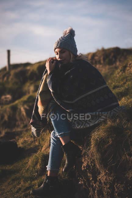 Thoughtful woman in shawl relaxing near beach — Stock Photo
